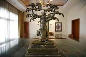 Meditating Buddha sitting under tree in decorated room — Stok fotoğraf