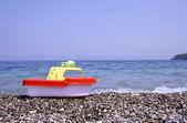 Rote und gelbe spielzeug kunststoff-boot am strand — Stockfoto