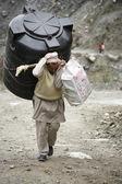 Man carrying water reservoir, annapurna, nepal — Stock Photo