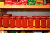 Jars of tomato sauce on the shelf in an organic shop — Stock Photo
