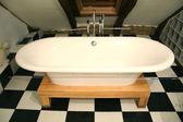 Bathtub view on a black and white tile floor — Stock Photo