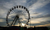Ferris wheel silhouette on cloudy sky — Stock Photo