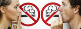 Couple smoking a no smoking sign — Stock Photo