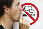 Man smoking a no-smoking sign — Stock Photo