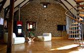 Vista de sala de estar con chimenea y pared de piedra antigua y moderna televisión — Foto de Stock