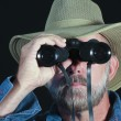 Royalty-Free Stock Photo: A Man in a Safari Hat Looks Through Binoculars