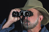 Un uomo con un cappello safari appare attraverso il binocolo — Foto Stock