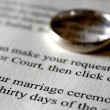 A Marriage Certificate and Gold Wedding Ring - Stock Photo