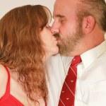 Среднем возрасте супружеская пара поцелуи — Стоковое фото