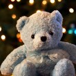 Blue teddy bear sits before background of shimmering Christmas tree lig — Foto Stock #8177205