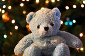 A blue teddy bear sits before a background of shimmering Christmas tree lig — Stock Photo