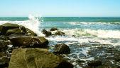 Onde si infrangono sulla riva rocciosa di un mare azzurro-verde — Foto Stock