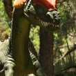 A Dilophosaurus Hunts in a Jurassic Forest - Stock Photo
