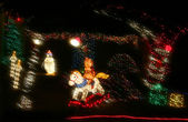 A Teddy Bear Rides a Rocking Horse in a Christmas Display of Lights — Stock Photo