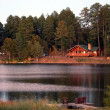 As Twilight Blankets the Cabins on a Mountain Lake - Stock Photo