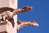 A pair of masonry gargoyles, or chimeras, the right one placid, the left sn — Stock Photo