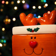 A Rudolph the Red Nosed Reindeer candy dish sits before a background of shi — Stock Photo