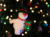 A Frosty the Snowman ornament hangs against a background of shimmering Chri — Stock Photo