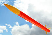 A Yellow and Orange Rocket Against a Cloudy Sky — Stockfoto