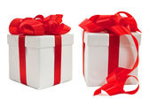 Set of white boxes tied with a red satin ribbon bow. — Stock Photo