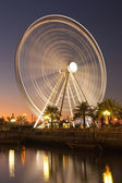 Big wheel against the evening sky and boats on the channel — Stock Photo