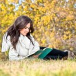 Beautiful woman reading the books in  autumn colored park — Foto Stock