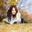 Beautiful girl with book lying on grass — Foto Stock