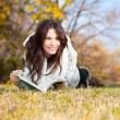 Beautiful girl with book lying on grass — Stockfoto