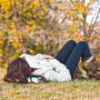 Beautiful girl with book sleeping  on grass — Stockfoto