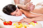 Beautiful brunette woman getting a back massage — Stock Photo