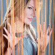 Woman peeking through the curtain - Stock Photo