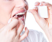 Young woman flossing teeth — Stock Photo