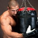 Athletic young man training kickboxing using black punching bag — Stock Photo