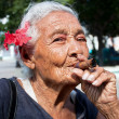 Stock Photo: Old wrinkled womwith red flower smoking cigar