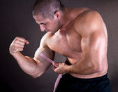 Young man measuring his perfect biceps — Stock Photo