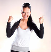 Champion woman standing with fists clenched in victory — Stock Photo