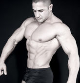 Athletic sexy attractive male body builder, demonstrating contest pose — Stock Photo