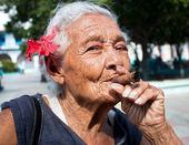 Old wrinkled woman with red flower smoking cigar — Stock Photo
