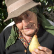 Senior woman with a pear — Stock Photo