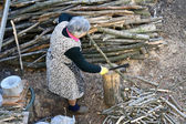 Senior woman cutting wood — Stock Photo