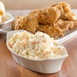 Coleslaw with fried chicken in background. — Stock Photo