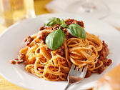 Spaghetti with basil garnish in meat sauce — Stock Photo