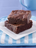 Two brownies stacked on a plate. — Stock Photo