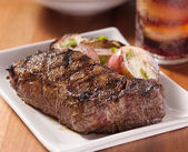 Grilled steak with potatoes and cola in background. — Stock Photo