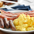 Breakfast meal with sausage and scrambled eggs with bacon. — Stock Photo #8630348