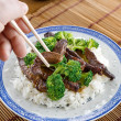 Eating chinese beef and broccoli with chopsticks — Stock Photo #8631775