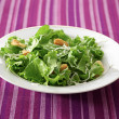A leafy green salad on a purple table cloth — Stock Photo