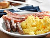 Breakfast meal with sausage and scrambled eggs with bacon. — Stock Photo