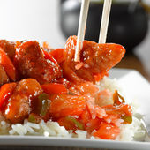 Sweet and sour pork on rice being eaton with chopsticks — Stock Photo