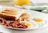 Petit déjeuner bacon, oeufs et pain grillé — Photo